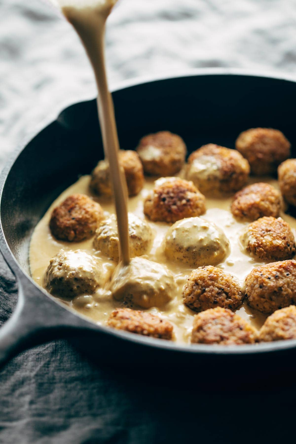 Meatballs in a pan with masala sauce drizzle.