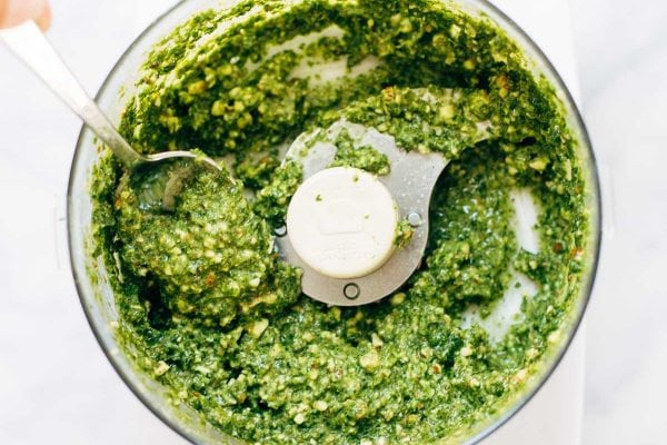kale pesto in a food processor with a spoon