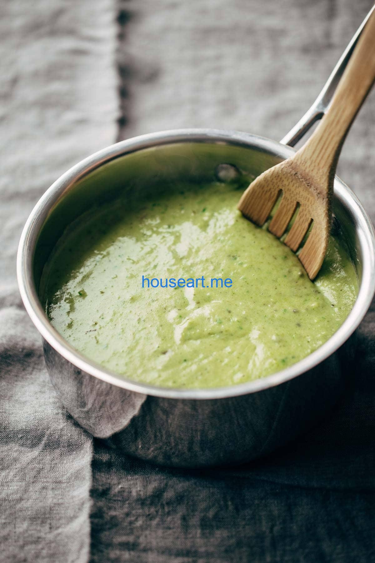 creamy spinach and roasted poblano sauce in a pan with a wooden spoon