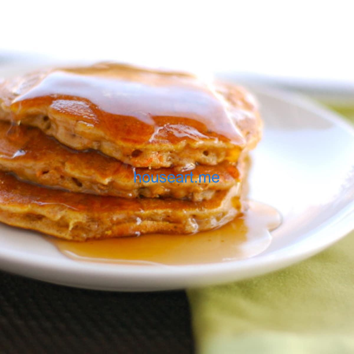 Cinnamon apple carrot pancakes with syrup drizzle on a white plate.