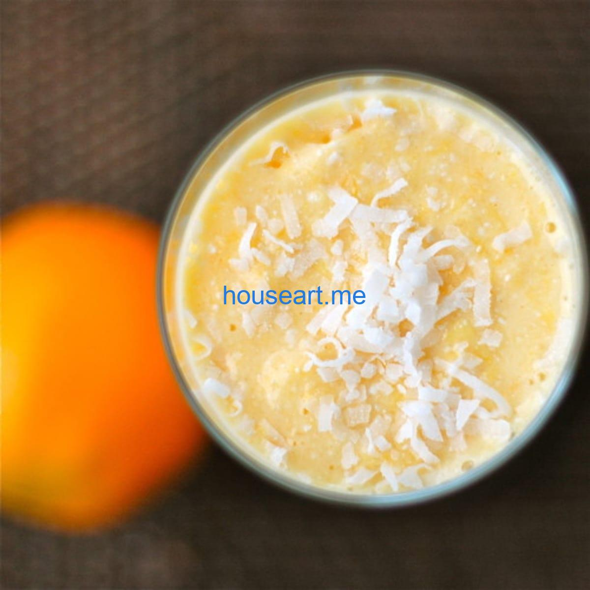 Coconut pineapple orange smoothie with coconut shreds on top.