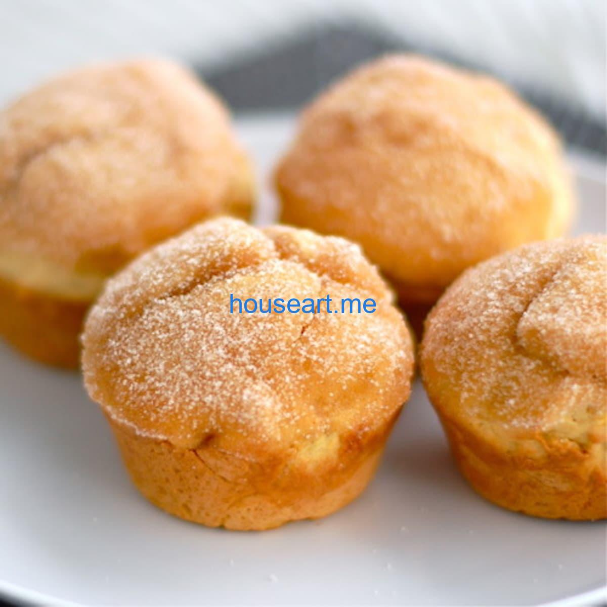 Four sugar-dusted sweet potato muffins.