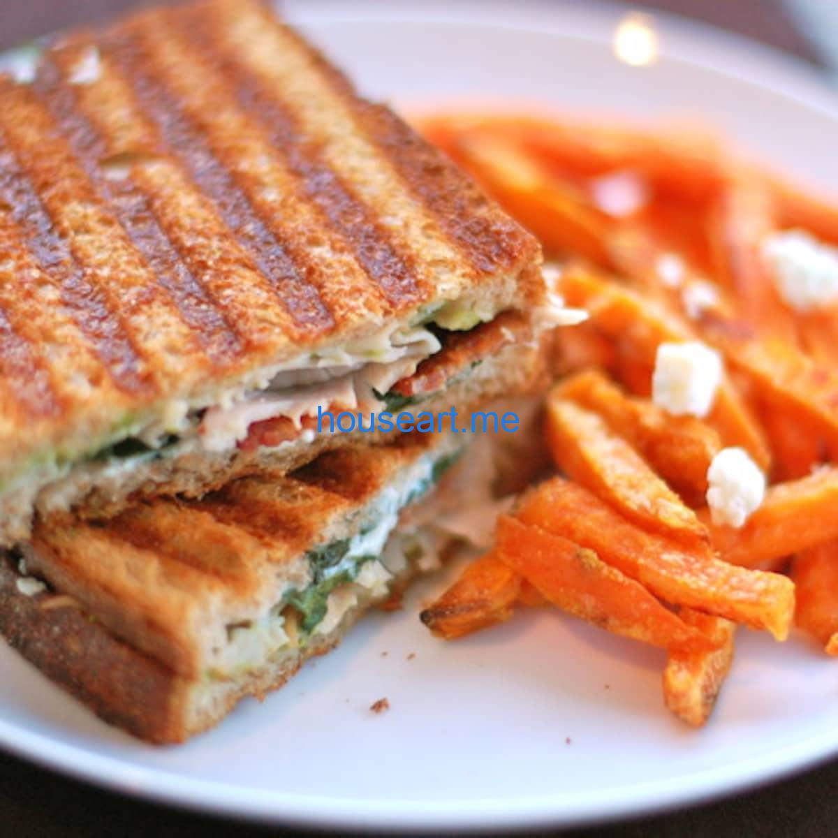 Gorgonzola and bacon panini with spinach on a plate with sweet potato fries.