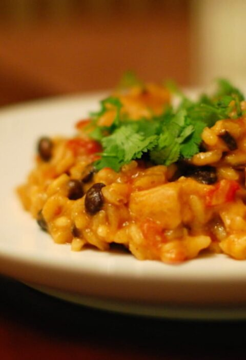 Cheesy black bean risotto on a white plate.