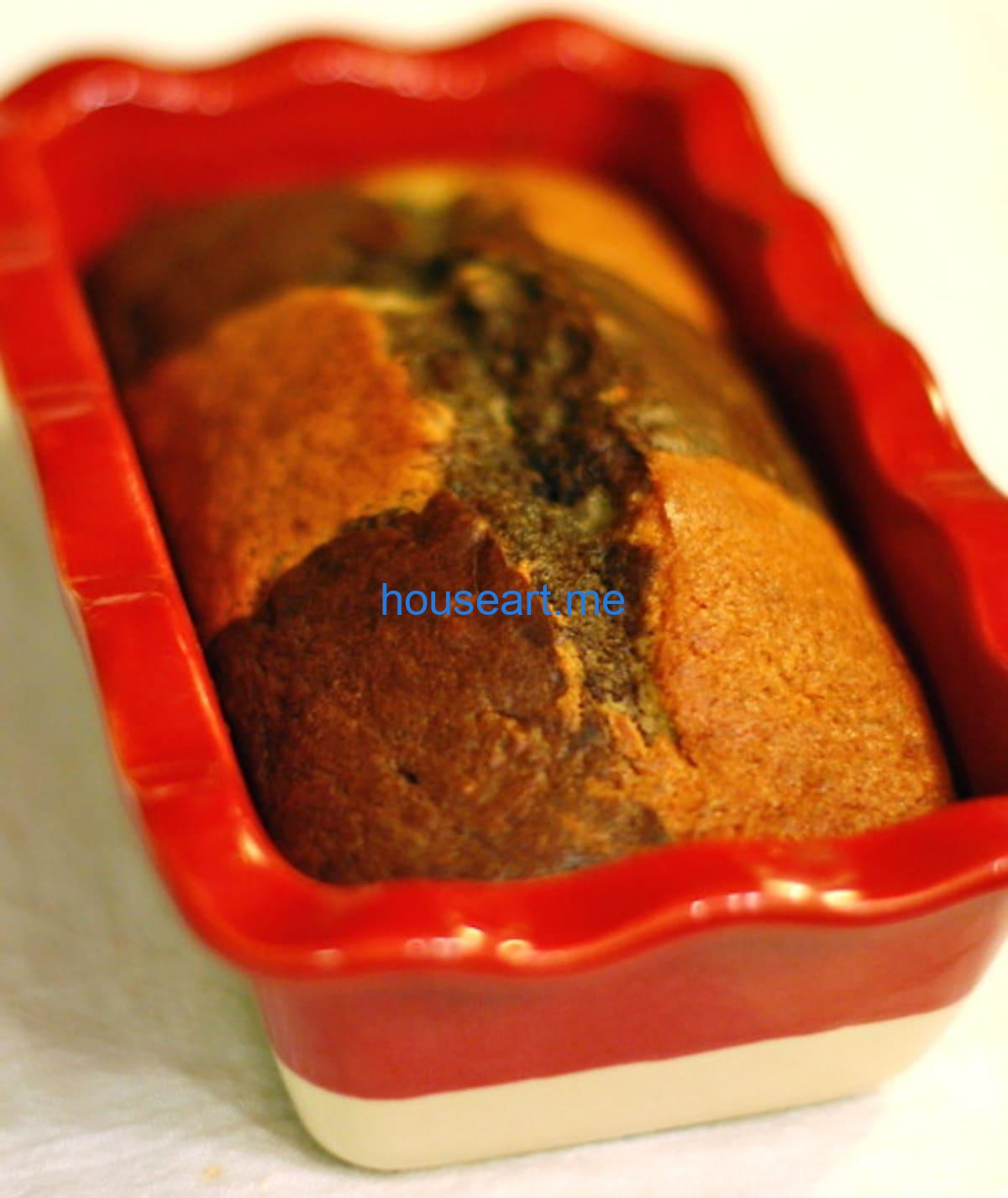 Loaf of chocolate checkered banana bread in a red baking dish.