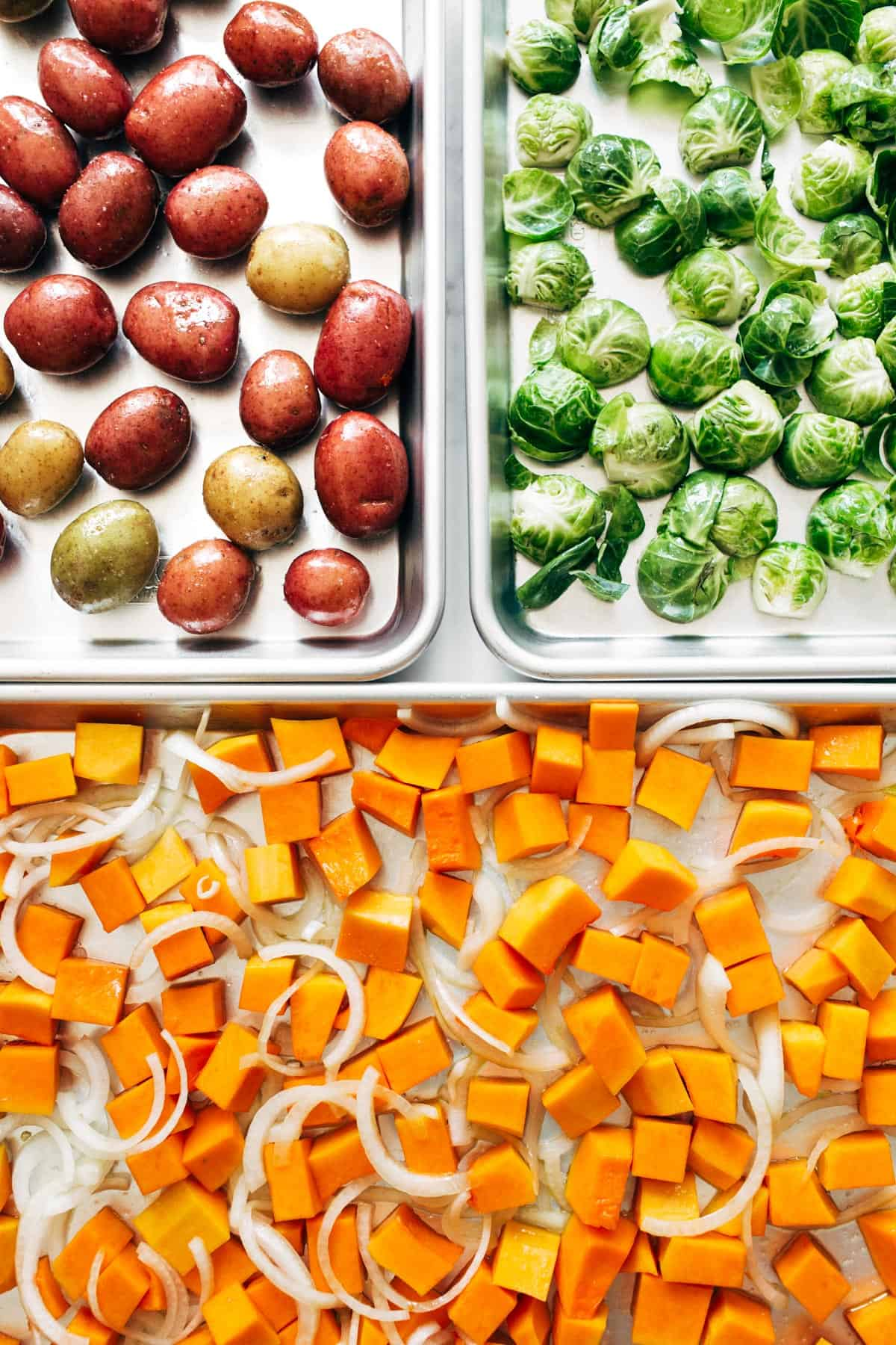 Potatoes, brussels sprouts, and squash on sheet pans.