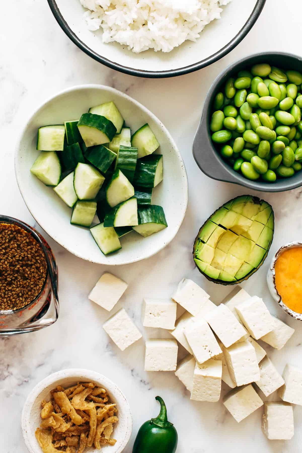 Ingredients in bowls for Crunchy Roll Bowls - rice, cucumber, edamame, tofu, avocado, sauce.